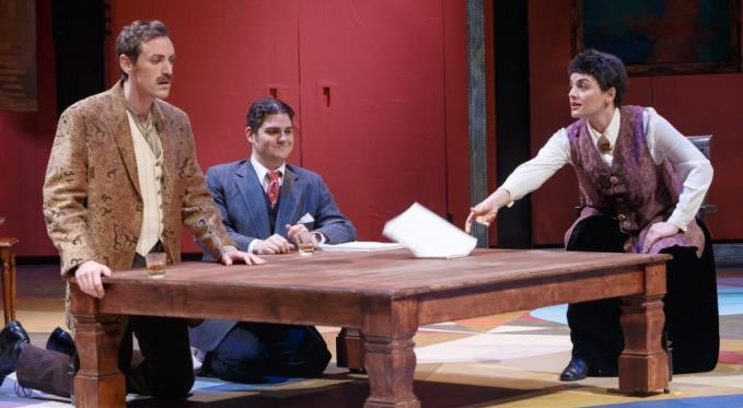Gertrude Stein (Laurel Semerdjian) offers 'feedback' on a surprised Ernest Hemingway's (Matthew Scollin) manuscript while an amused F. Scott Fitzgerald (Adam Bonanni) watches. Photo via David Bachman Photography.
