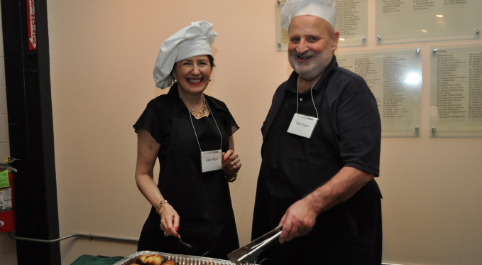 Former board member Ellen Roth and Bob Egan serve the entree at a recent Volunteer Stars dinner.