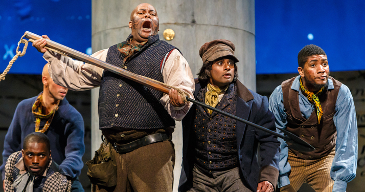 Queequeg (Musa Ngqungwana) leads a whaling boat as Greenhorn (Sean Panikkar) watches him try to spear a whale.