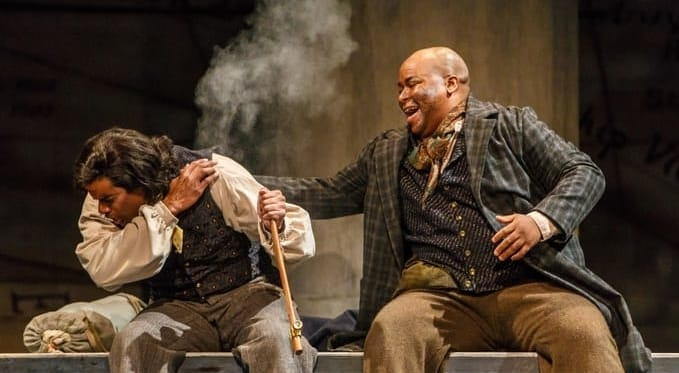 Queequeg (Musa Ngqungwana) laughs as Greenhorn (Sean Panikkar) coughs after taking a hit from Queequeg's pipe.